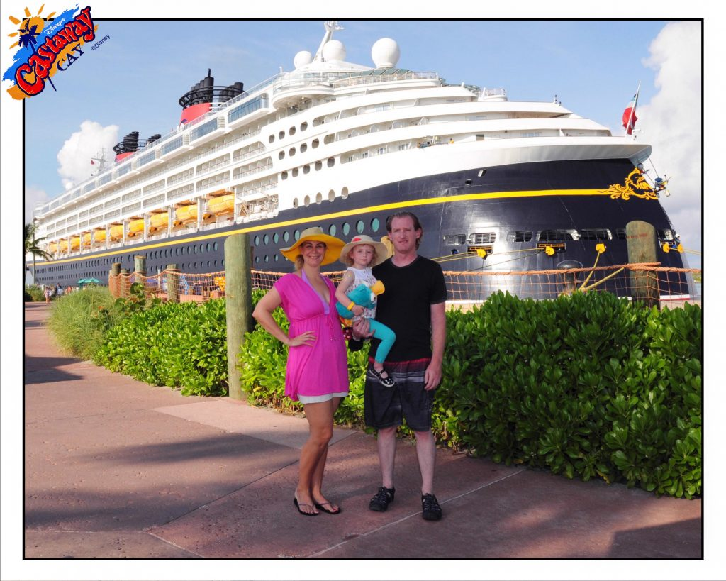 a couple holds a small child in front of huge disney cruise ship