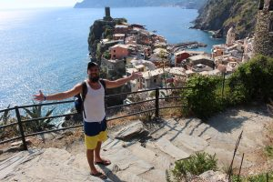 a man with arms wide and the cliff side town in Cinque Terre Italy behind him
