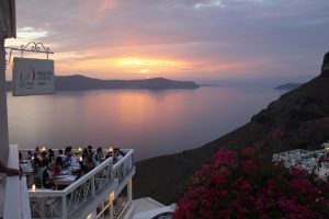 a stunning sunset of the bay with a restaurant balcony to the side in Oia Greece
