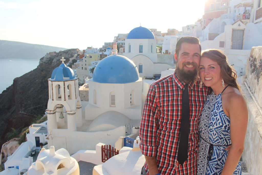 a honeymoon couple stand together with the white washed, blue domed houses of Santorini behind them