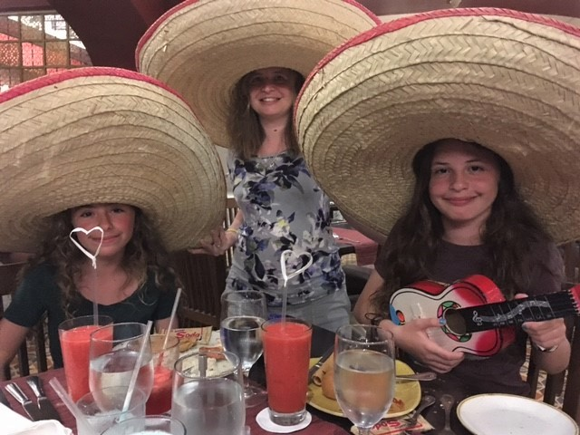 two young girls and their mother sit at the table in giant sombreros on a family trip to Mexico