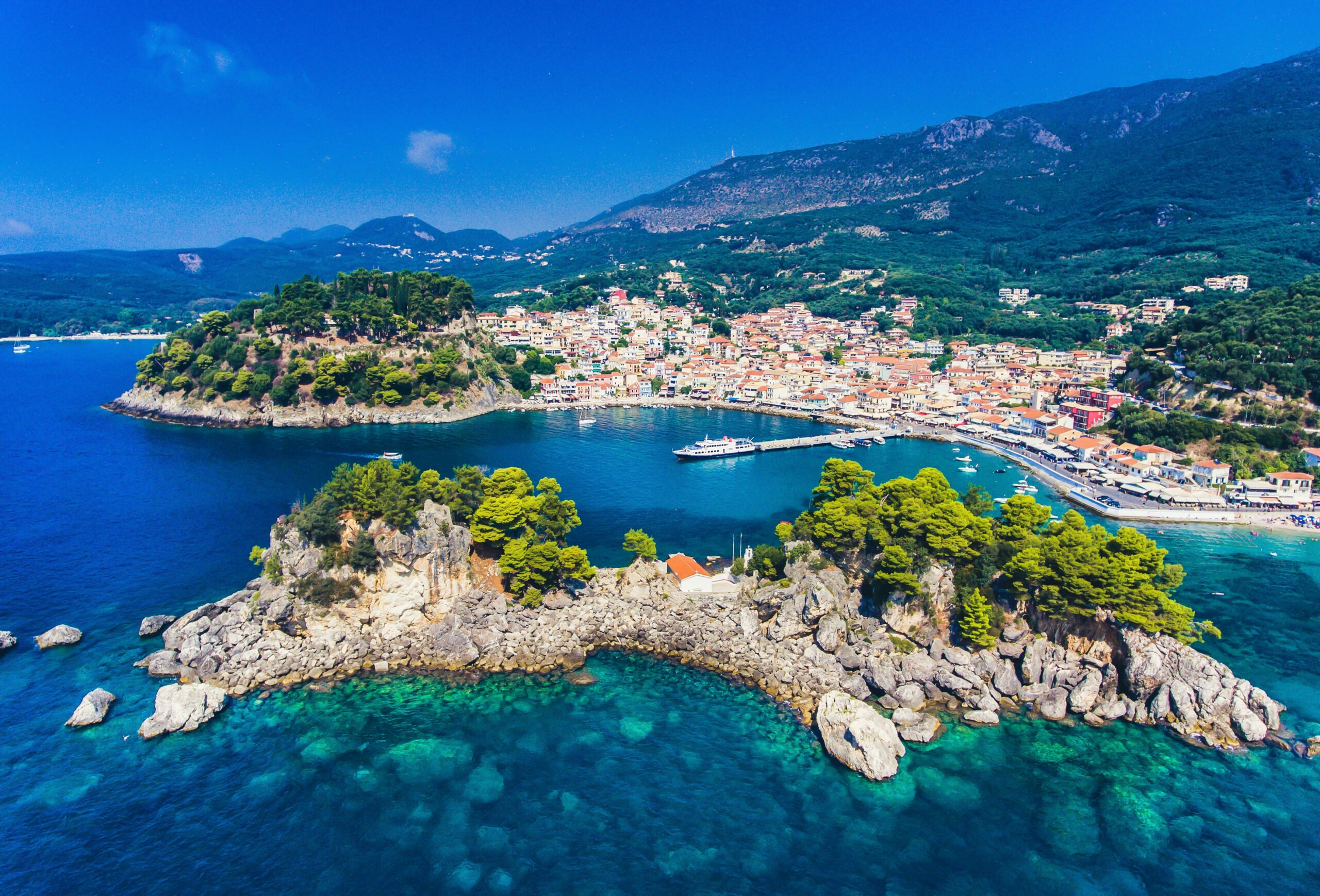 aerial view of Parga bay, blue waters and a villiage in the green mountainous terrain in Greece