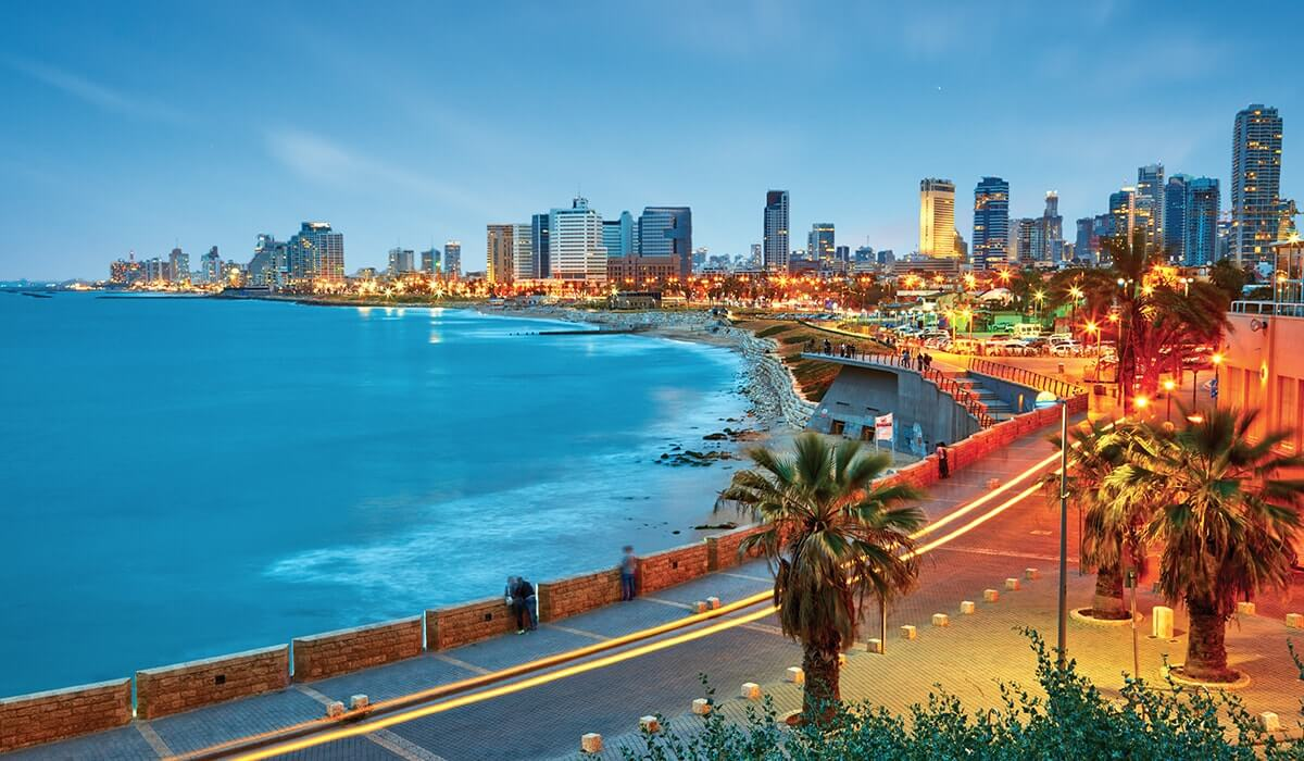 look down the coast as it curves around - beautiful blue sea on one side and the tall buildings of Tel Aviv at night
