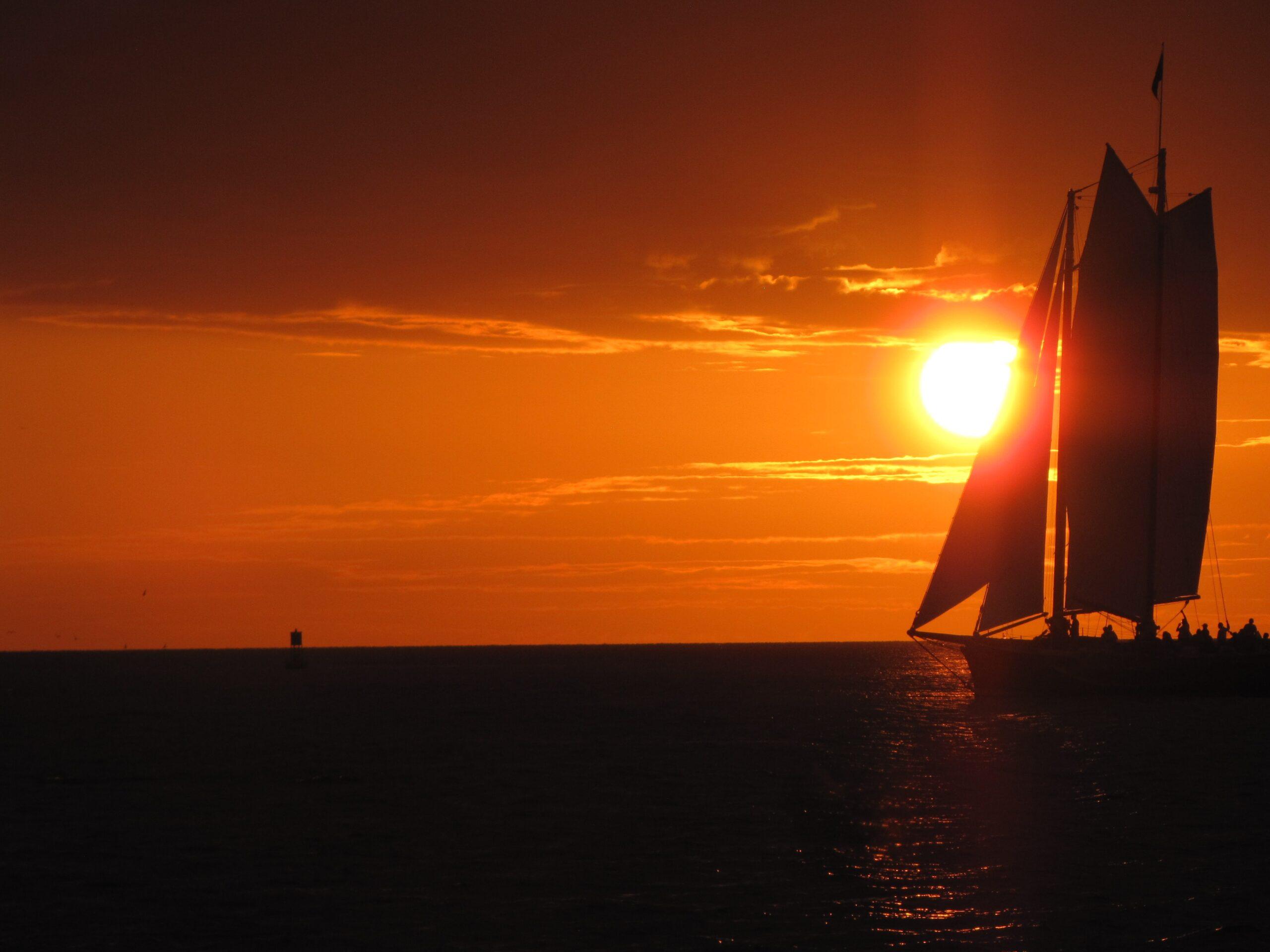 a sailboat against a bright orange sunset in Key West Fl