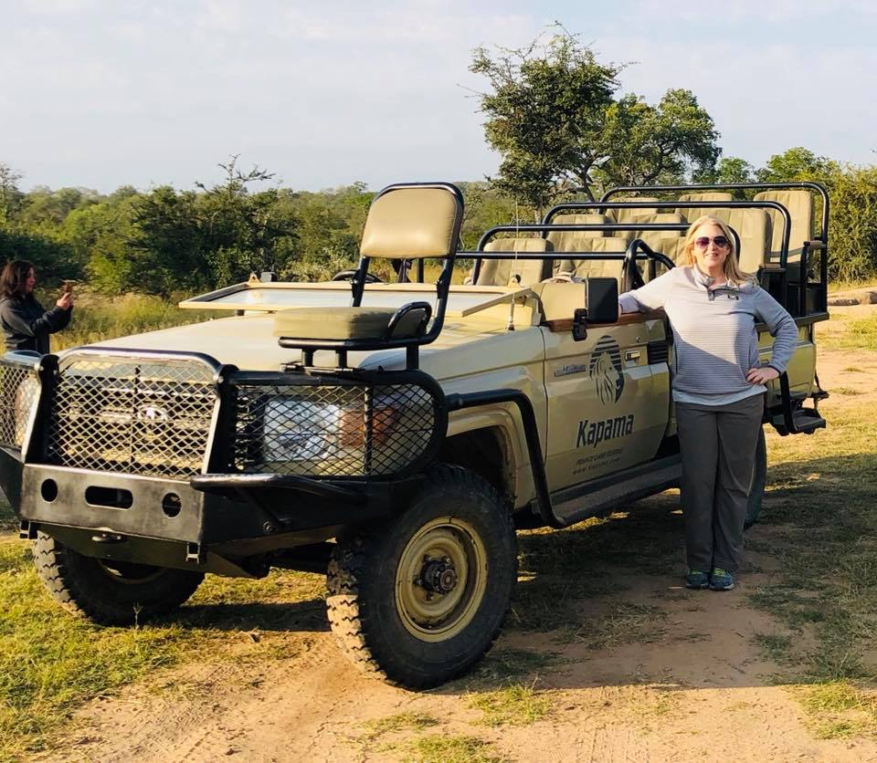 woman standing next to a open-top safari jeep in South Africa