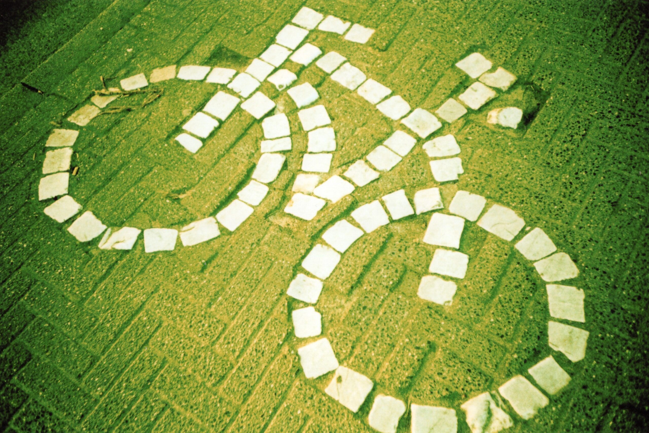 aerial view of a large bicycle shape made out of white stones on green grass