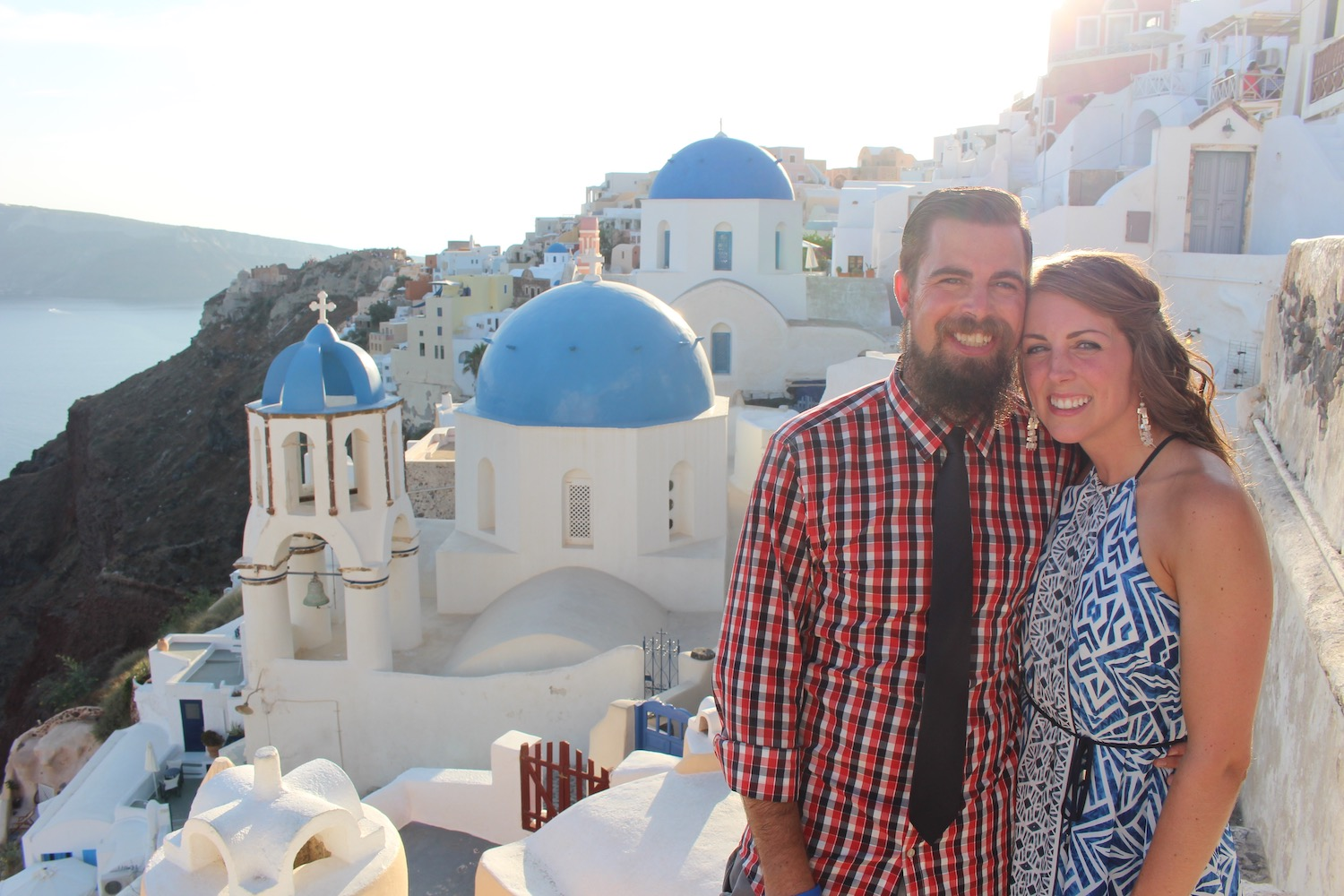 a couple in front of the blue and white houses of Santorini Greece