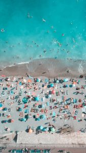 aerial view of a beach with the light blue water on top and the grey pebbles covered with people on towels and pastel colored umbrellas in Page Beau Rivage inNice France