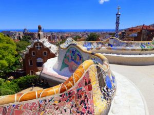 a curves wall covered in mosaics on a terrace overlooking the city of Barcelona at Gaudi's Park Guell