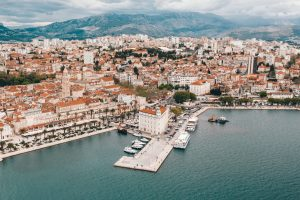 an aerial view of downtown Split Croatia with the harbor and red tiled roofs and mountains in the background
