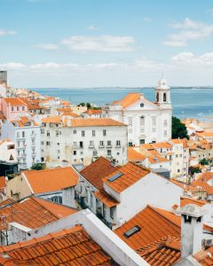 a view of red tiled roofs and white buildings including a small tower with the sea in the background looking from a height in Lisbon Portugal