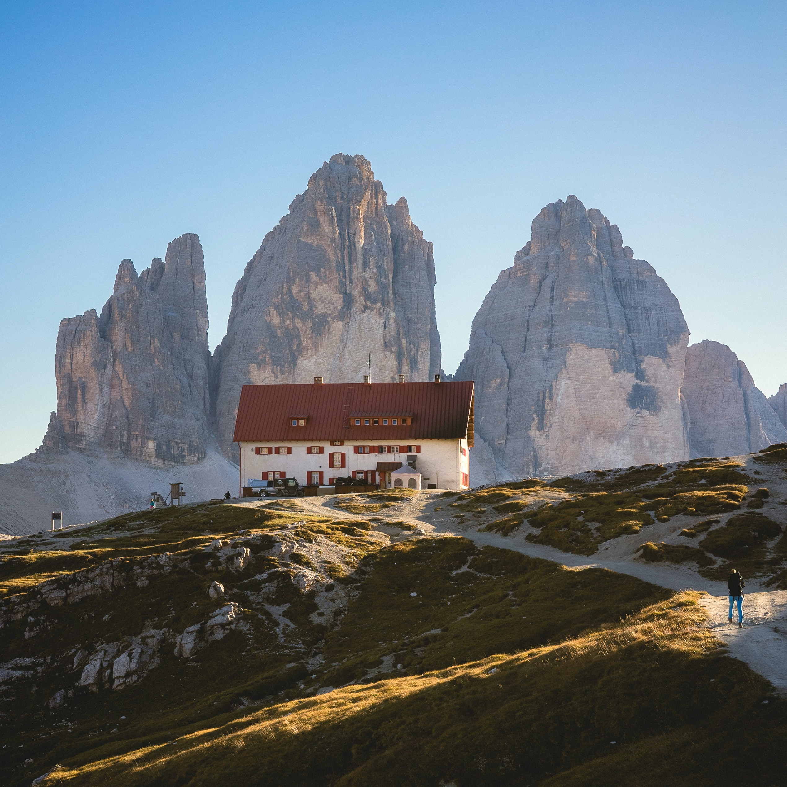 three imposing mountain spires behind a inn on a hill in the Dolomites