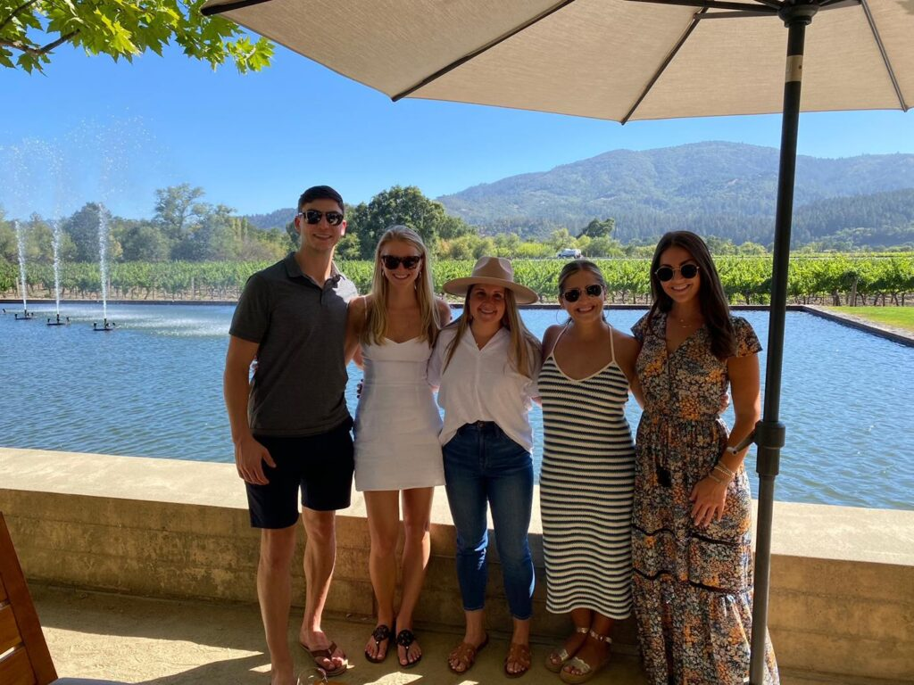 a group stands in front of a large fountain and beautiful vineyards in Napa Valley CA