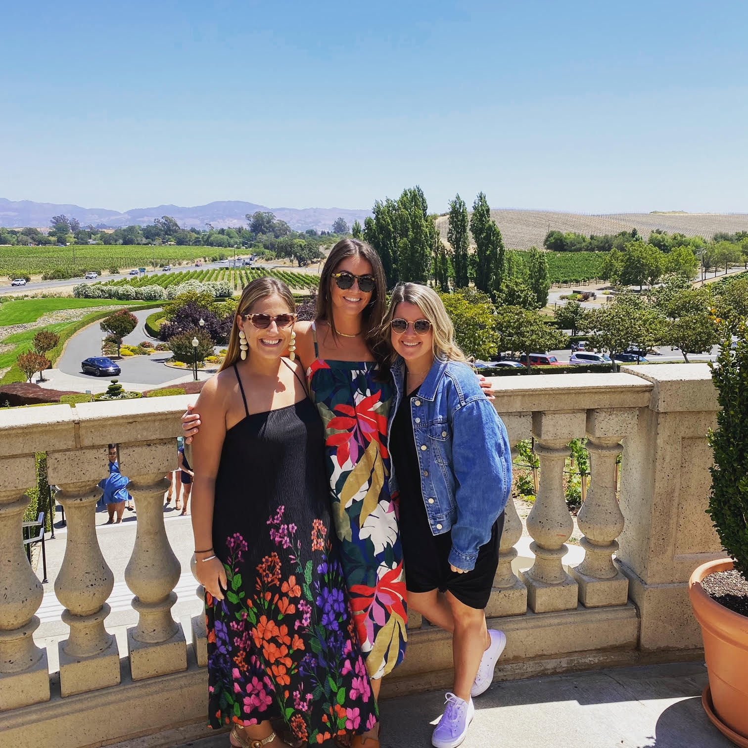 three women pose on the columned balcony with the vineyards of Napa Valley CA behind them
