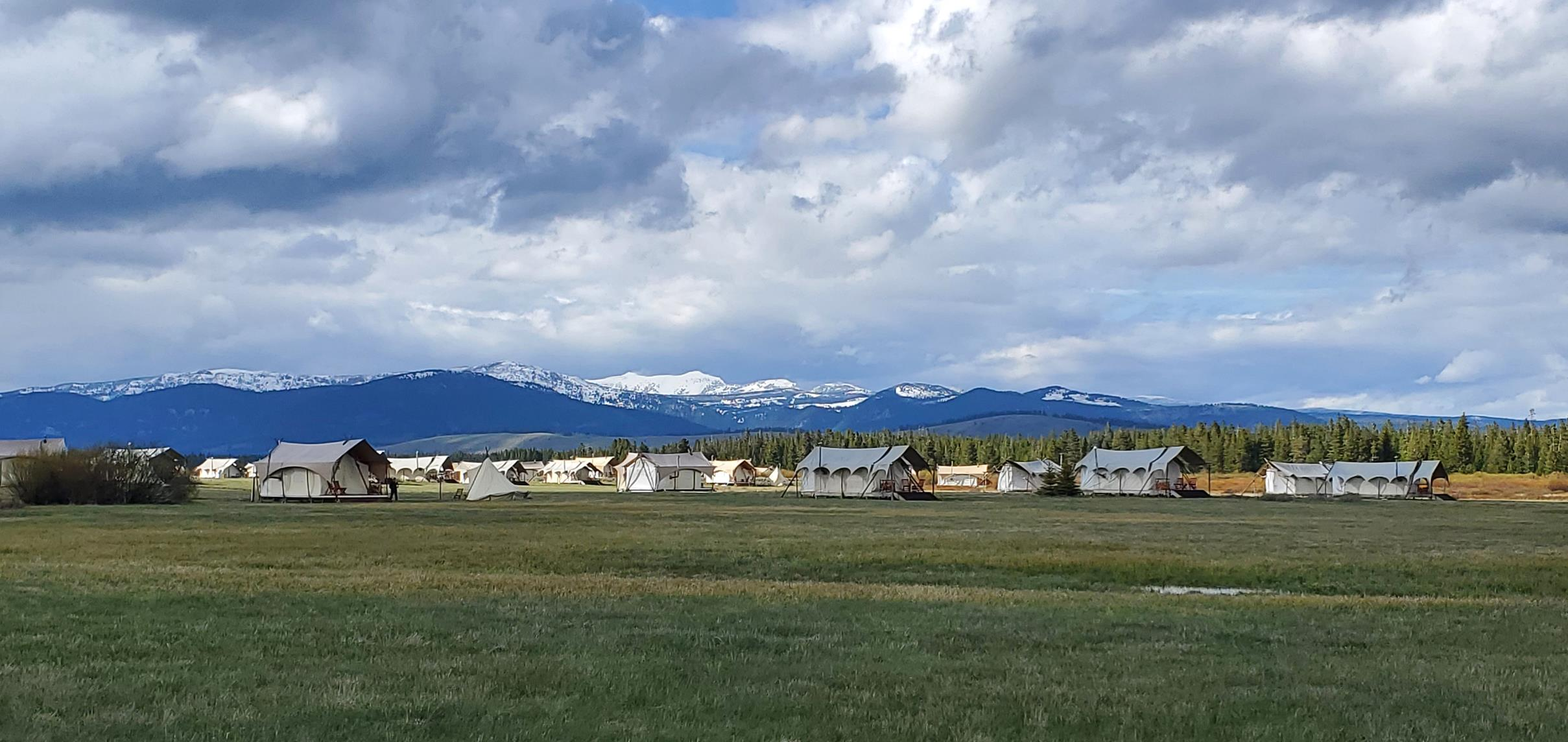 stunning snow-capped mountains set behind a Glamping campsitein Wyoming