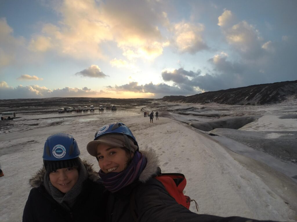 two women in parkas and hard hats take a selfie with the sunrise in the background on a glacier in Iceland