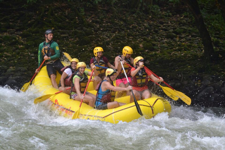 a group of friends white water rafting down a river in Costa Rica