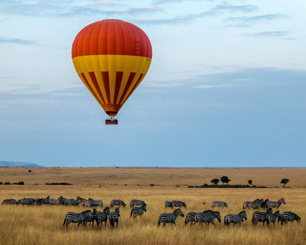 a red and yellow hot air balloon over a herd of zebras on safari in Tanzania