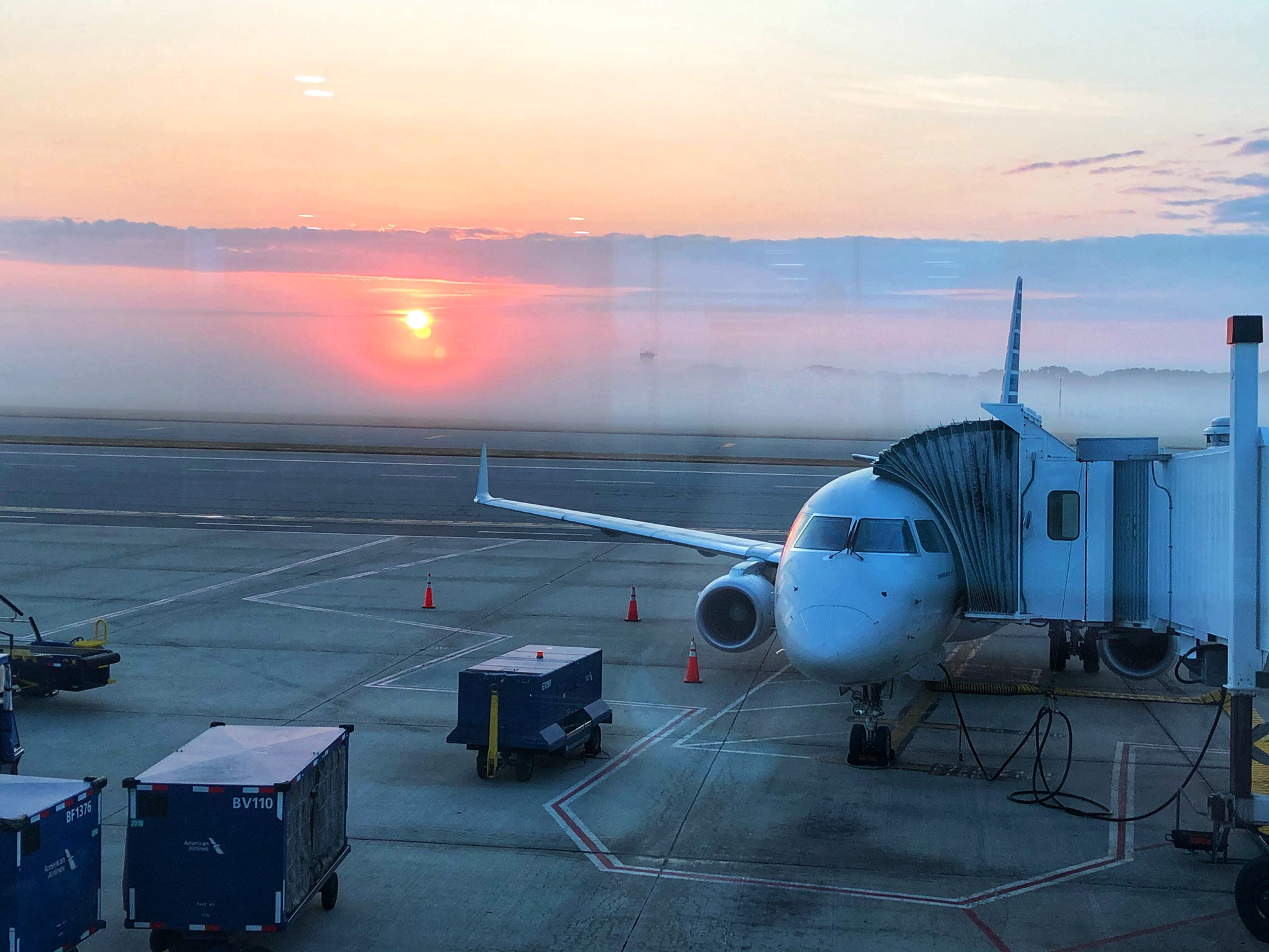 A plane on the tarmac and a stunning sunset behind